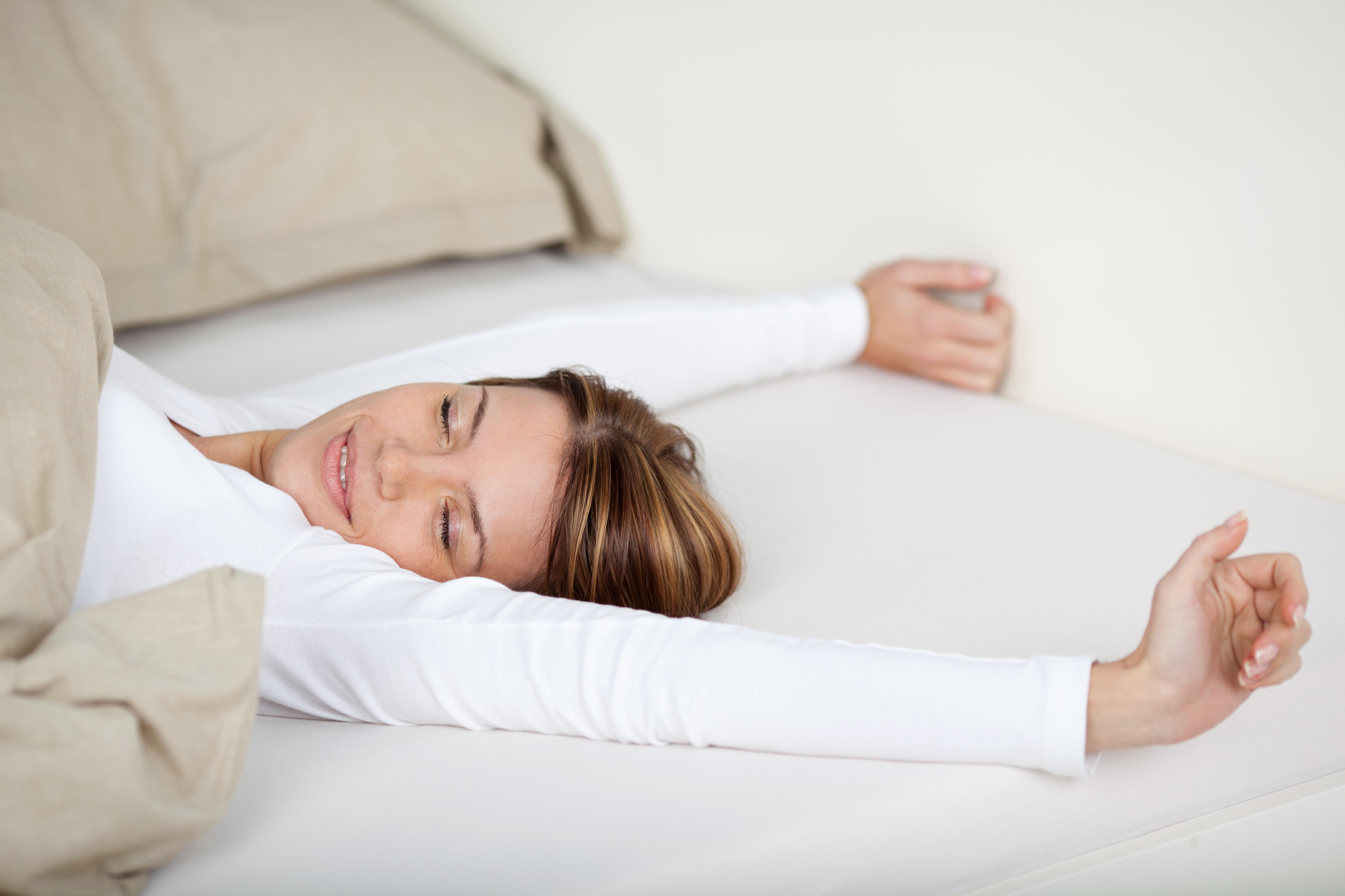 Lächelnde Frau streckt sich auf 7-Zonen-Taschenfederkern-Matratze